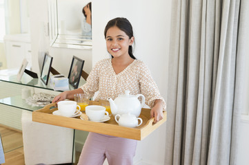 Smiling girl carrying tea on a serving tray