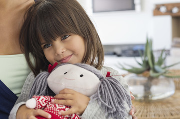 Close-up of a girl sitting with her mother and holding a rag doll