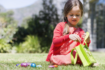 Girl picking up Easter eggs in a lawn