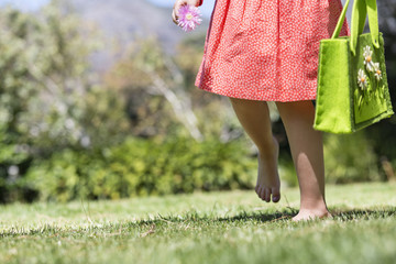 Low section view of a girl walking in a lawn