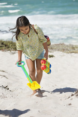 Girl carrying shovel and toy on the beach