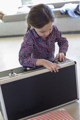 Girl trying to close a suitcase