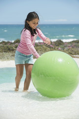 Girl playing with a fitness ball on the beach