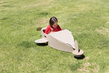 Girl playing with a cardboard airplane in lawn