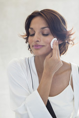 Woman cleaning her face with a cotton pad