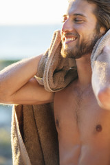 Happy man wiping himself with a towel on the beach