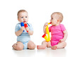 Babies girl and boy  playing musical toys. Isolated on white bac