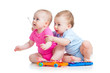 Little children girl and boy play musical toys. Isolated on whit