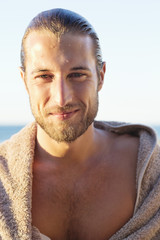 Portrait of a man wrapped in a towel and smiling