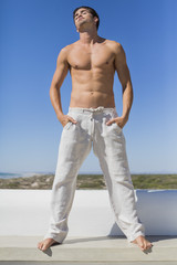 Shirtless man standing with hands in pockets