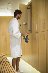 Man putting his shoes in a locker room at spa
