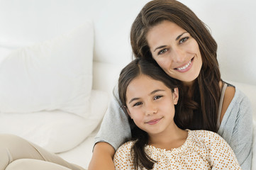 Portrait of a woman and her daughter smiling