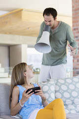 Man shouting into a megaphone at his daughter for playing video game