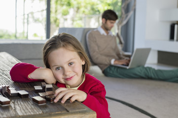 Portrait of a smiling girl with her father using a laptop in the background