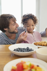 Man feeding his daughter