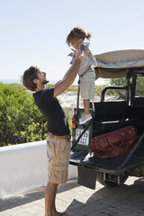 Man playing with his daughter beside a SUV