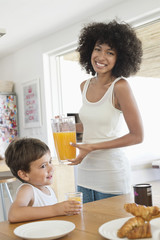 Woman and her son at a dining table with orange juice