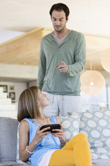 Man scolding his daughter for playing video game