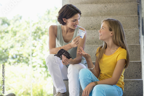 Woman giving pocket money to her daughter