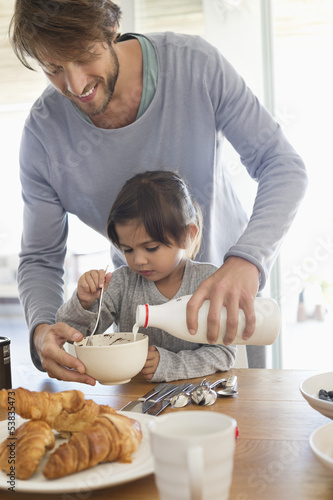 Man giving milk to his daughter