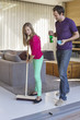 Girl cleaning floor with a mop beside her father