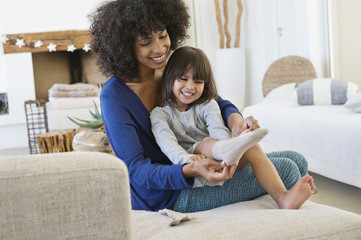 Woman putting on socks to her daughter and smiling