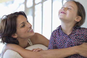 Woman smiling with her daughter at home