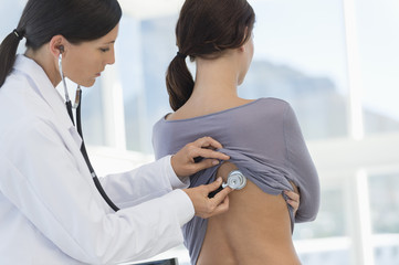 Female doctor examining a woman's back with a stethoscope