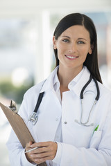Female doctor holding a clipboard and smiling