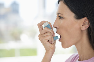 Close-up of a woman using an asthma inhaler