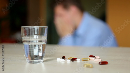 depressed young man. taking a pill.