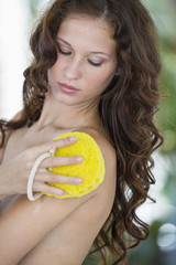 Woman cleaning her body with bath sponge