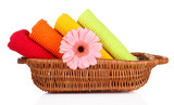 Colorful towels and flower in basket, isolated on white