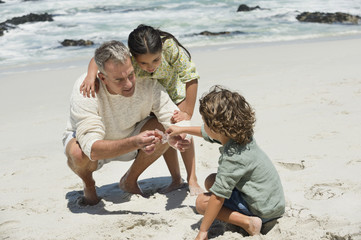 Children with their grandfather on the beach