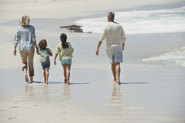Children walking with their grandparents on the beach