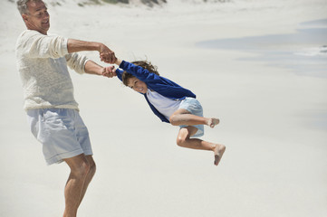 Man playing with his grandson on the beach
