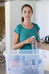 Portrait of a woman holding a bottle in front of a recycling bin