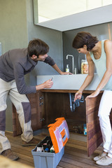 Woman discussing with a man repairing kitchen sink