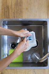 Woman washing dishes in a domestic kitchen