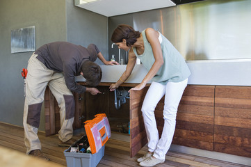 Man examining a kitchen sink with a woman standing beside him