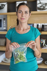Woman packing leaf vegetables for storage
