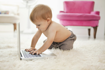 Baby boy playing with a laptop
