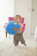 Baby boy playing with a globe ball