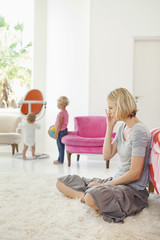 Woman sitting on a rug with her children playing in the background