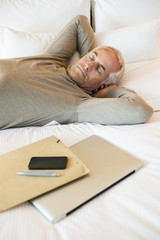 Man resting on the bed with a laptop and file in a hotel room