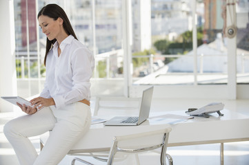 Businesswoman using a digital tablet while sitting on a table in an office
