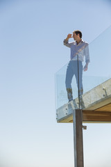 Man standing on the terrace and shielding his eyes