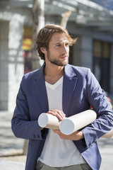 Architect carrying paper rolls