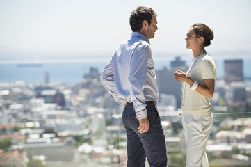 Couple discussing on a terrace with city in the background