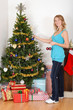 blonde woman hanging christmas ornament on tree